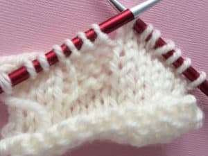Work up until to YO. Wrap the yarn counter-clockwise around the right needle. Then, work the next stitch normally.