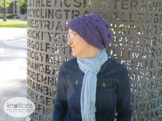 A woman wearing a deep purple worsted-weight knit hat. She is shown in profile. The ribbing of the hat sits a little loose on her forehead. There is a cabled band above the ribbing of the hat. The hat falls in a slouch at the back of her head.