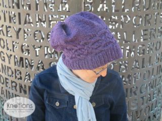 A woman wearing a deep purple worsted-weight knit hat. She is shown looking down towards the ground, you can see the top of the hat. The cable band is shown going around the head just above the ribbing. It is a Celtic knot style cable that runs end-to-end around the circumference of the hat. The top of the hat has gathers where the stitches were pulled in.