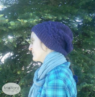 A woman wearing a deep purple worsted-weight knit hat. She is shown in profile. The ribbing of the hat covers her ears. At the back of her head, the ribbing comes to the edge of the scarf she is wearing. The hat falls in a slouch off the back of her head.