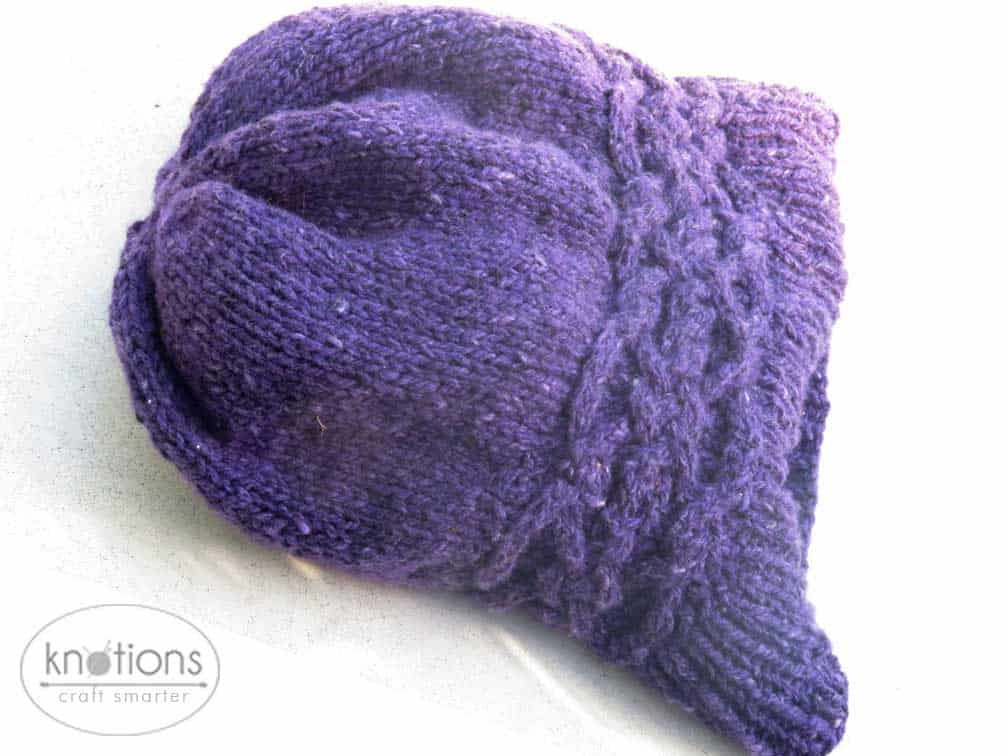A purple worsted-weight knit hat laying flat. The hat has a ribbed brim, and a stockinette main body. Just above the ribbing, there is a celtic-knot style cable band that is knit horizontally. The top of the hat is gathered in slightly.
